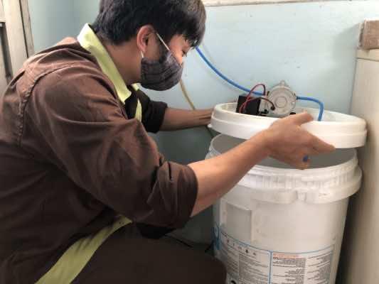 Thanh niên nhà máy kiểm tra dung dịch cồn trước khi phun khử khuẩn tại buồng